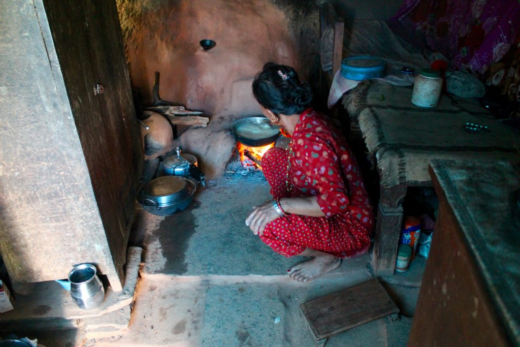 Rural Nepali woman cooking in kitchen